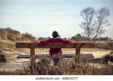 A woman with a ponytail is relaxing on a wooden bench enjoying the nature