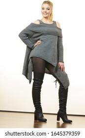 Mujer con cola de ponilo usando túnica gris de suéter largo, pesas negras. Elegante equipo otoñal.