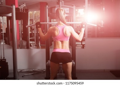 woman with a ponytale wearing pink and black professional sportswear doing exercises with an iron barbell at the highly equipped sun lightened gym. fitness and workout concept