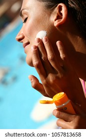 Woman at the pool applying sun cream on her face