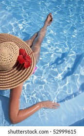 Woman in a pool hat relaxing in a blue pool