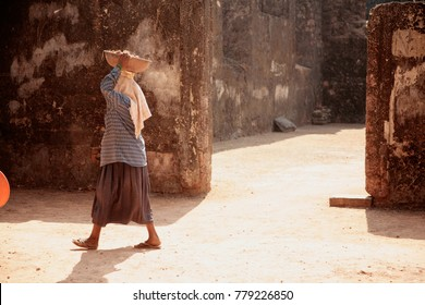 A woman in poor clothes with a load on her head walking down the street in the slums of the Indian city