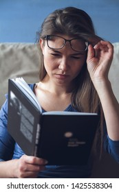 Woman with poor eyesight problems is reading a book with glasses. Eye fatigue concept or astigmatism.