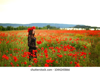 woman in a poppy field in a dress. a beautiful sexy woman stands in a poppy field at sunset, holding a bouquet of flowers from poppies. relax and romance in one shot
