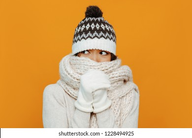 Woman portrait. Accessories. Warmness. Asian girl in a white scarf, cap and gloves is showing she is cold, on an orange background