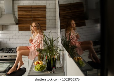 Woman portrait. Adorable, sexy and smiling girl in pink silk pajama, sitting on the kitchen table and holding a glass of champagne. At home, modern interior.