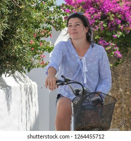 Woman portrait at Andros island in Greece on top of a bicycle against a background of flowers.