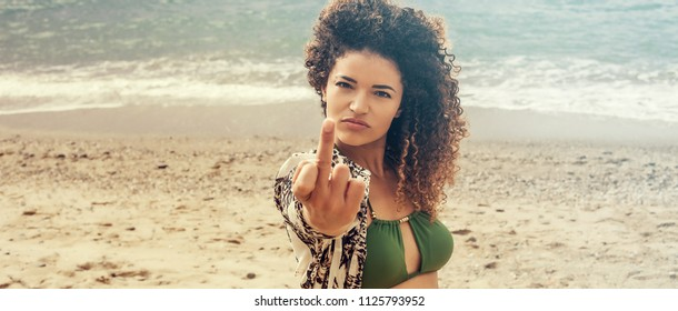 Woman portrait at the beach giving the finger, letterbox