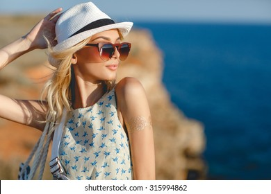 woman portrait. beautiful young blonde girl in white hat and sunglasses standing on sea background. sea view, freedom and summer concept. summer sunny portrait. outdoor