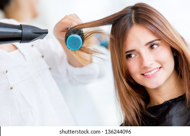 Woman portrait blow drying her hair at the beauty salon