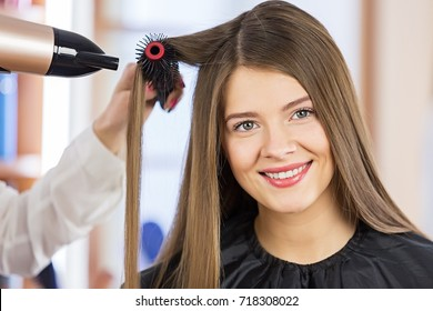 Woman portrait blow drying her hair at the beauty salon.