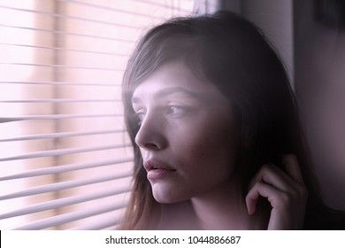 Woman portrait; close up portrait of a young woman looking through the window.