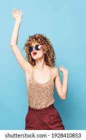 Woman portrait Curly haired sunglasses holds a hand above the head of the mod sequin shirt