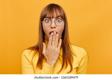Woman portrait. Emotion. Shock. Beautiful young woman in eyeglasses is covering her mouth feeling shocked, on a yellow background