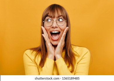 Woman portrait. Emotion. Surprise. Beautiful young woman in eyeglasses is feeling surprised, on a yellow background