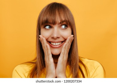Woman portrait. Emotion. Young woman is touching cheeks, looking away and smiling, on a yellow background