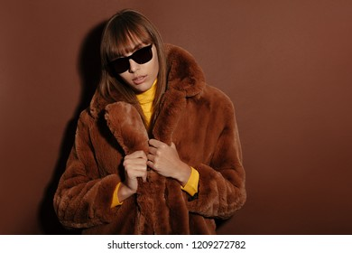 Woman portrait. Fashion. Girl is posing in a fur coat and sun glasses on a brown background