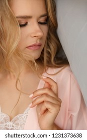 Woman portrait. Fashion model. Blonde gorgeous young girl looking at camera with a discerning eye. Portrait of adorable blonde woman in gentle silk pajama.