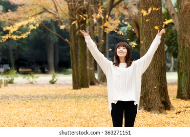 Woman portrait of happy lovely and beautiful Japanese young woman in forest in fall colors.