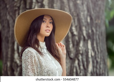 Woman - portrait of happy lovely and beautiful mixed race Asian Caucasian young girl outdoor against big tree in the park bokeh background