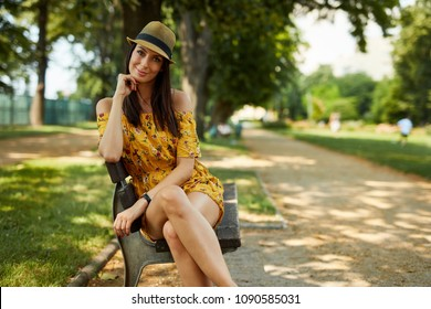 Woman portrait - Happy young woman in the city park outdoor in summer wearing yellow summer dress and trendy hat sitting on bench.