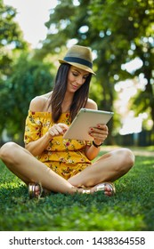 Woman portrait - Happy young woman in the city park outdoor in summer wearing summer dress and trendy hat sitting on grass