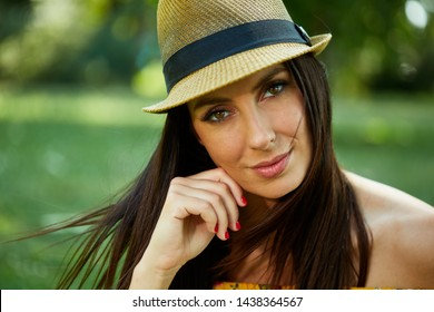 Woman portrait - Happy young woman in the city park outdoor in summer wearing yellow summer dress and trendy hat.