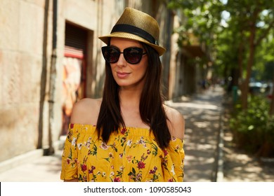 Woman portrait - Happy young woman on the street outdoor in summer wearing sunglasses and trendy hat.