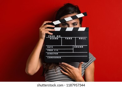 Woman portrait holding movie clapper against colorful red background.