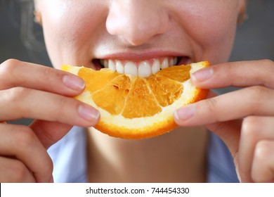 Woman portrait holds in her hand a slice of chopped orange eats her for breakfast with her mouth in the kitchen concept of a healthy diet.