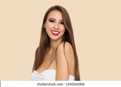 Woman portrait. Makeup. Beautiful young brown-haired woman is looking at camera and smiling, on a beige background