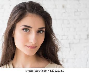 Woman portrait natural beautiful casual beautiful people. Studio shot. Stone wall background.