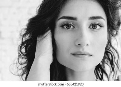Woman portrait natural beautiful casual beautiful people. Studio shot. Stone wall background black and white