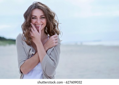 Woman Portrait on the beach. Happy beautiful curly-haired girl close-up, the wind fluttering hair. Spring portrait on the beach. Young pretty girl. Young smiling woman outdoors portrait. Close. ocean.