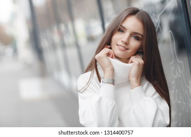 woman portrait outdoors. smiling girl in the street in warm sweater
