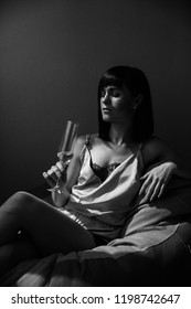 Woman portrait at party. Lovely, beautiful, young girl in gentle silk pajama, holding a glass of champagne, posing while sitting on the bed. Indoors. Black and white photo.