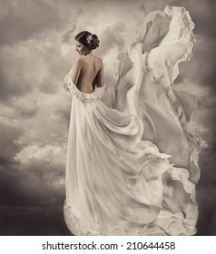 woman portrait in retro dress, artistic white blowing gown, waving and fluttering fabric, fantasy wedding bride with naked back
