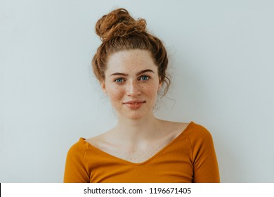 Woman portrait. Style. Beautiful blue eyed girl with freckles is looking at camera with a tender smile, on a white background