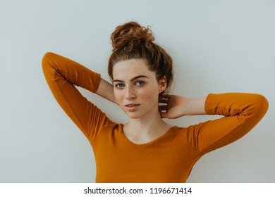 Woman portrait. Style. Beautiful blue eyed girl with freckles is raising her hands while posing at camera, on a white background