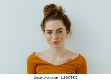 Woman portrait. Style. Beautiful blue eyed girl with freckles is looking at camera and smiling, on a white background