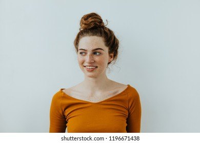 Woman portrait. Style. Beautiful blue eyed girl with freckles is looking away and smiling, on a white background