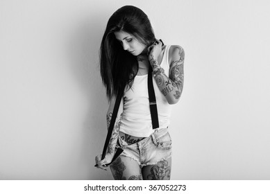 Woman portrait with tattoo and suspenders against white wall. Black and white image.