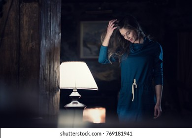 woman portrait wearing casual dress smiling and looking down near lamp it living room at rural home indoor. Europe Alps. Winter evening