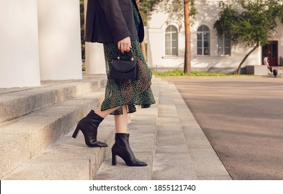 woman pose in black ankle boots with mini bag on the stairs, street style outfit