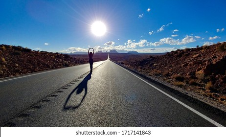 A woman poses in center frame along a lonely stretch of highway headed towards Monument Valley, UT. Several concepts are portrayed such as freedom, success, and relaxation.