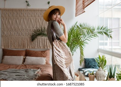 Woman Posing in  boho apartments. Stylish decor, home plants. Cozy time.