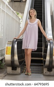 Woman posing by an escalator