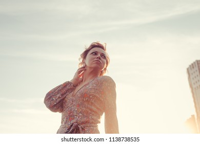 Woman posing to the camera on the sunset on a warm summer day