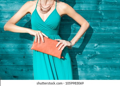Woman posing in dress, wearing necklace, and holding purse. Colorful fashion background and accessories concept.