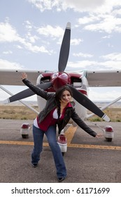 A woman posing in front of an airplane.